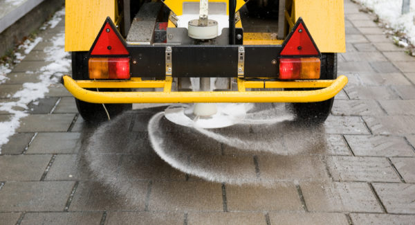 A machine is sprinkling salt on a sidewalk